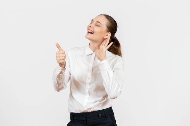 正面図白いブラウスの若い女性が白い背景の女性の仕事場の感情感モデルをよく聞い