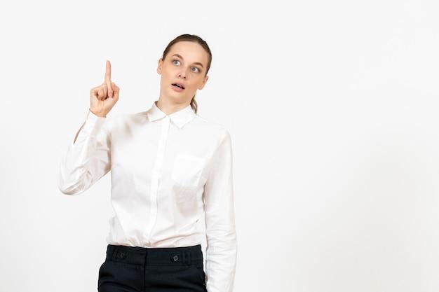 白い背景の上の彼女の指を上げる白いブラウスの正面図若い女性ジョブオフィス女性の感情モデルの感情