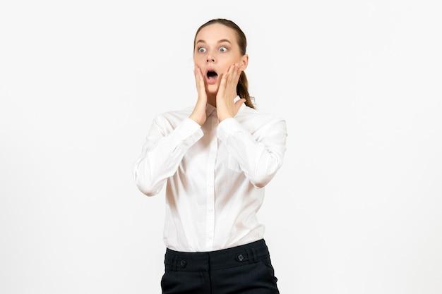 Вид спереди молодая женщина в белой блузке с потрясенным лицом на белом фоне офисная работа женские эмоции чувство модели