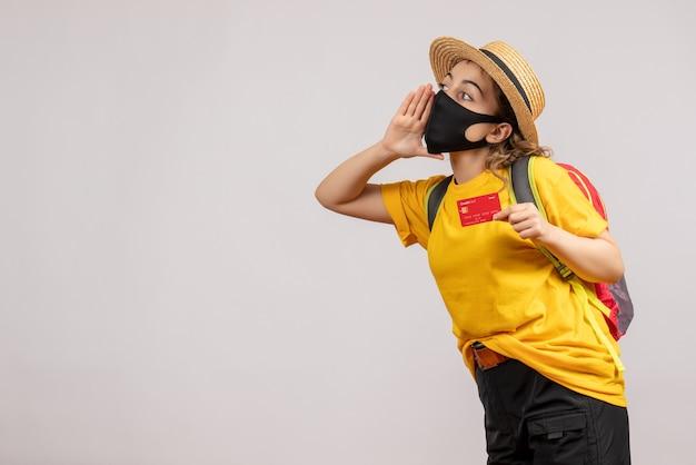 카드를 들고 노란색 티셔츠에 전면보기 젊은 여자