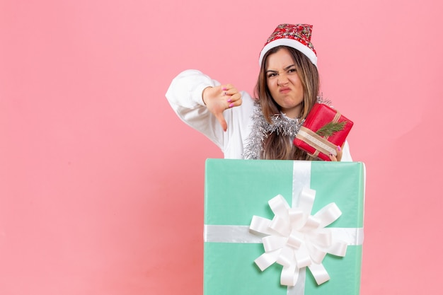 Front view of young woman inside present holding another present displeased on pink wall