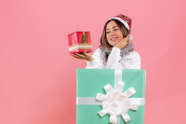 Front view of young woman inside present holding another present on light pink wall