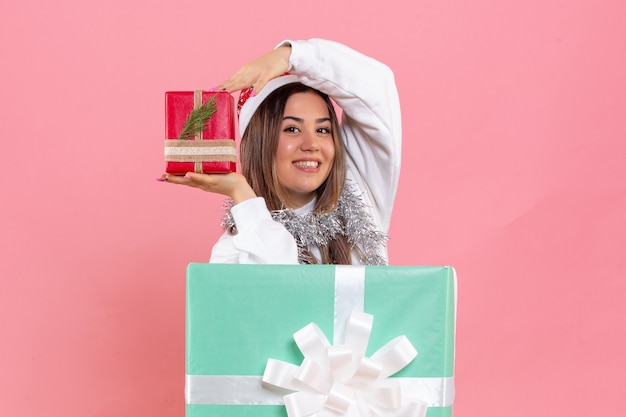 Front view of young woman inside present holding another present on a pink wall