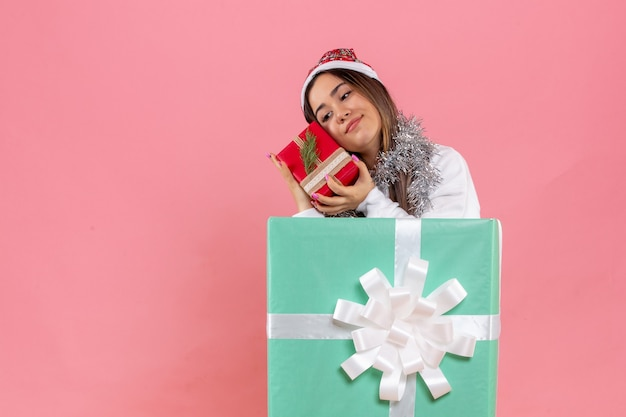 Front view of young woman inside present holding another present on pink wall