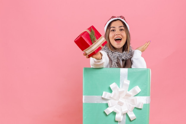 Front view of young woman inside present holding another present on the pink wall