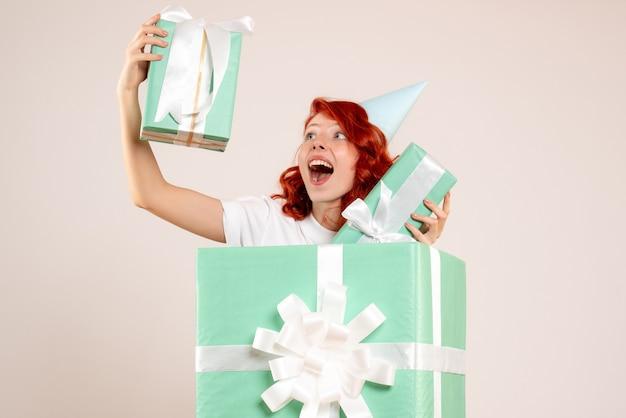 Вид спереди молодая женщина внутри настоящего, держащая другие подарки на белом фоне