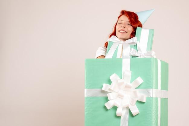 Вид спереди молодая женщина внутри настоящего, держащая другие подарки на белом столе