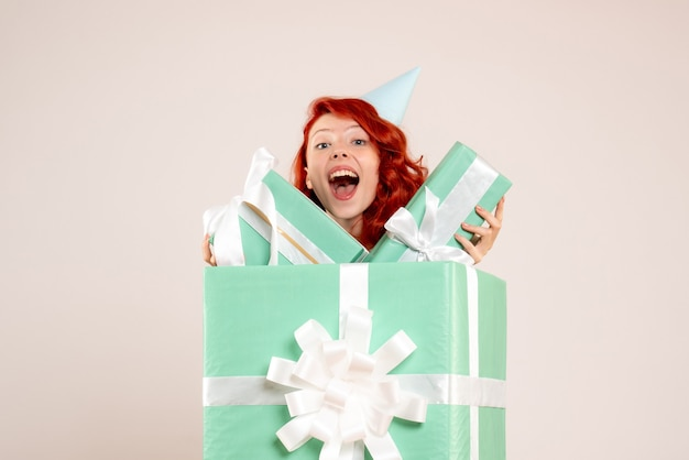 Front view young woman inside present holding other presents on white background