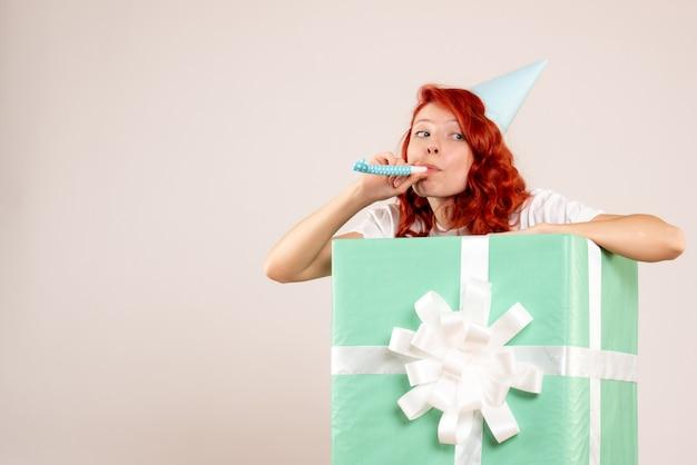 白い背景の上のキャップとプレゼントの中の正面図若い女性