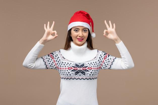Giovane donna di vista frontale che sorride appena sul nuovo anno marrone di natale di emozione del fondo