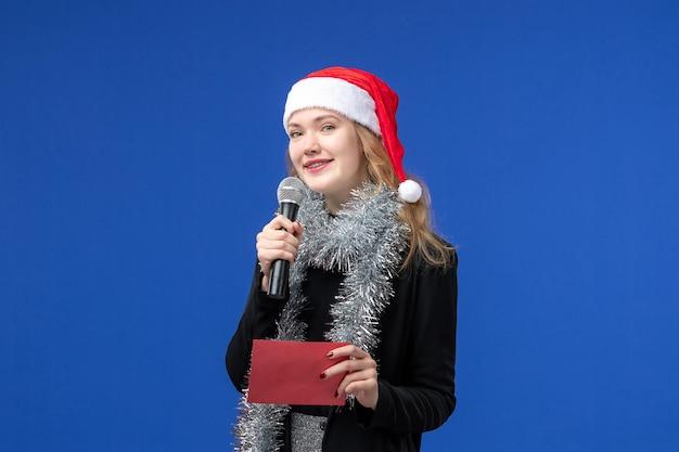 Vista frontale della giovane donna alla festa di karaoke con busta sulla parete blu