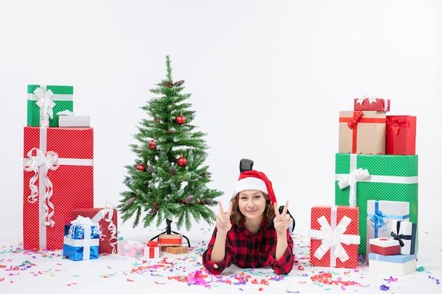 Vista frontale della giovane donna che posa intorno ai regali di natale e al piccolo albero di festa sulla parete bianca