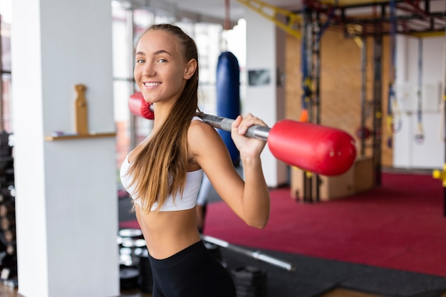 Front view young woman lifting weights