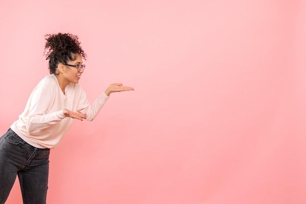Vista frontale della giovane donna sulla parete rosa chiaro