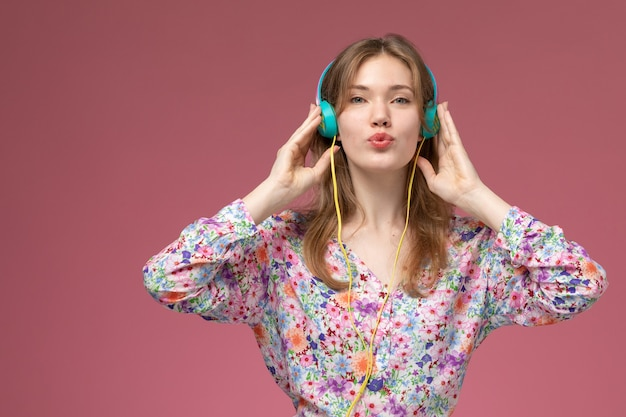 Молодая женщина вид спереди слушает песню и держит наушники ближе к себе