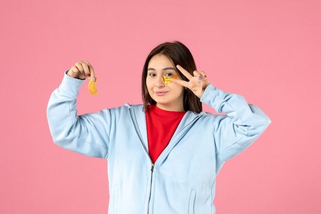 Vista frontale della giovane donna che fa una maschera sul muro rosa