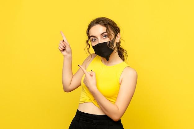 Vista frontale della giovane donna in maschera sul muro giallo chiaro