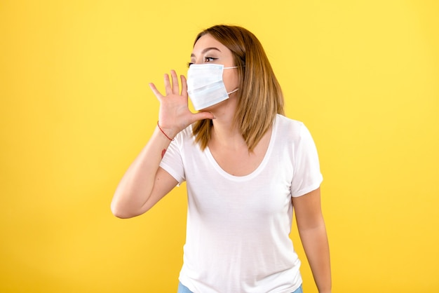 Front view of young woman in mask on yellow wall