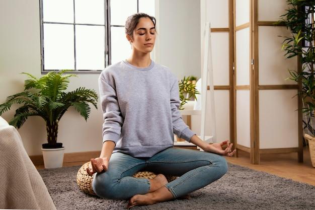 Vista frontale della giovane donna che medita a casa