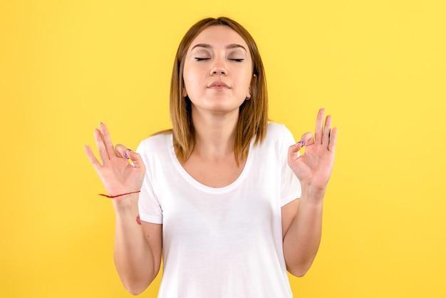 Vista frontale della giovane donna che medita sulla parete gialla