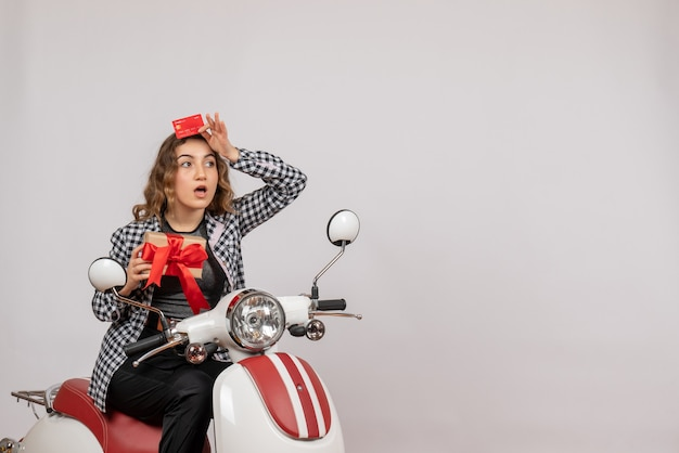 Front view young woman on moped holding card and gift