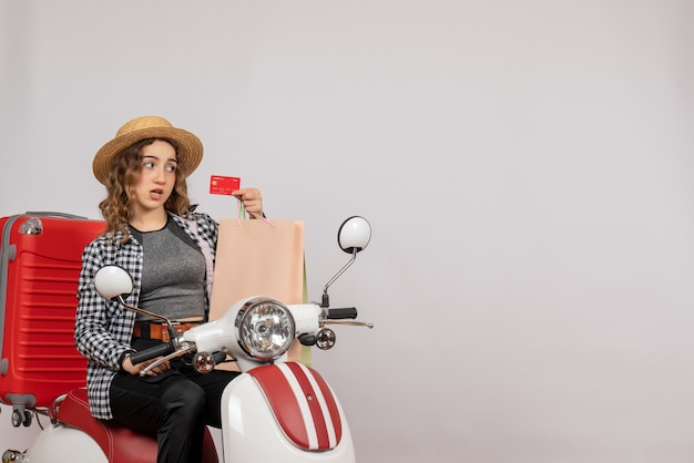 Front view young woman on moped holding up card