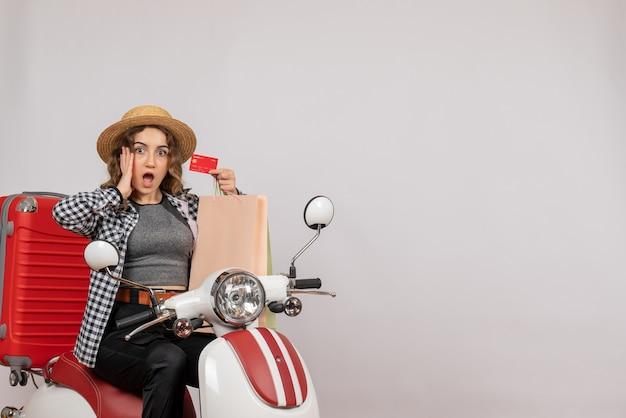 Vista frontale della giovane donna sul motorino che sostiene la carta