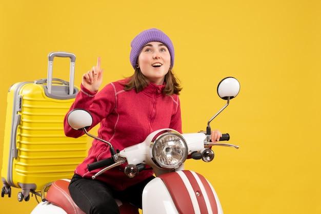Vista frontale giovane donna sul ciclomotore che punta il dito verso l'alto