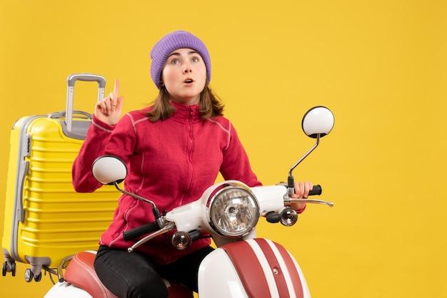 Giovane donna di vista frontale sul ciclomotore che indica con il dito in su