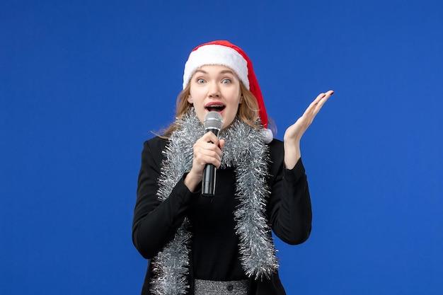 Vista frontale della giovane donna nella festa di karaoke di capodanno sulla parete blu