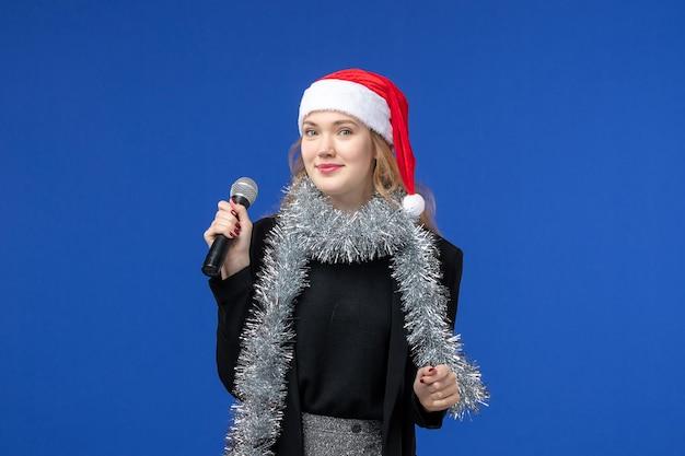 Vista frontale della giovane donna alla festa di karaoke di capodanno sulla parete blu