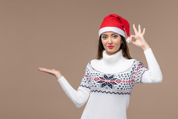 ダークブラウンの背景の休日の感情のクリスマスの正面図若い女性
