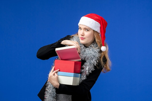 Vista frontale della giovane donna che apre i regali di capodanno sulla parete blu