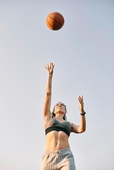 Вид спереди молодая женщина играет в баскетбол в одиночку