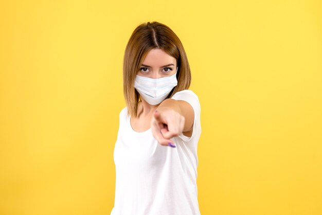 Vista frontale della giovane donna che punta nella maschera sulla parete gialla