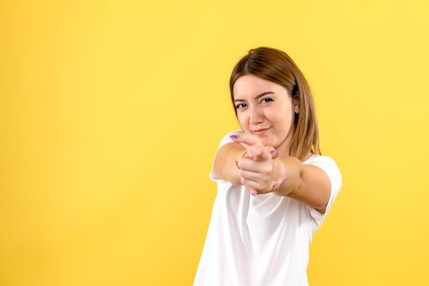 Vista frontale della giovane donna che punta sulla parete gialla