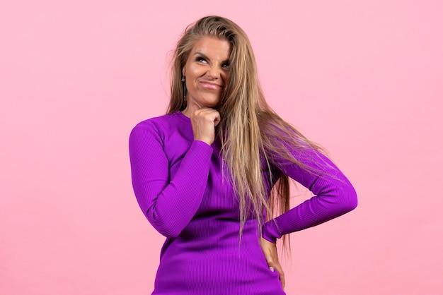 Vista frontale della giovane donna in posa in bellissimo abito viola sul pavimento rosa modello di bellezza posa donna color