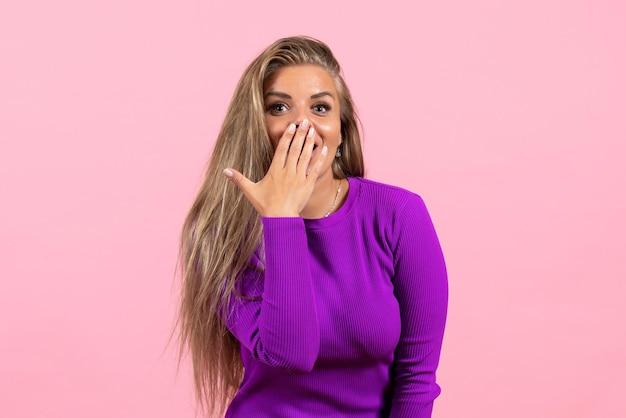 Vista frontale della giovane donna in posa con un bellissimo vestito viola sulla parete rosa