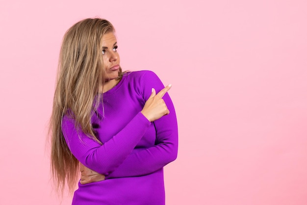 Front view of young woman posing in beautiful purple dress on pink wall