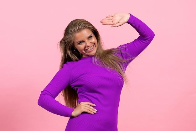 Vista frontale della giovane donna in posa sorridente in bellissimo abito viola sulla parete rosa