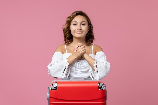 Vista frontale della giovane donna in posa e sorridente con borsa da vacanza rossa sulla parete rosa pink