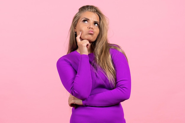 Front view of young woman posing and thinking in beautiful purple dress on pink wall