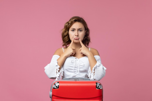 Vista frontale della giovane donna in posa con la sua borsa rossa sul muro rosa