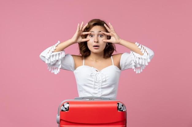 Vista frontale della giovane donna che posa con la borsa rossa delle vacanze sulla parete rosa chiaro