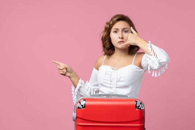 Vista frontale della giovane donna in posa con la borsa da vacanza rossa sul pavimento rosa modello viaggio vacanza mare viaggio colore