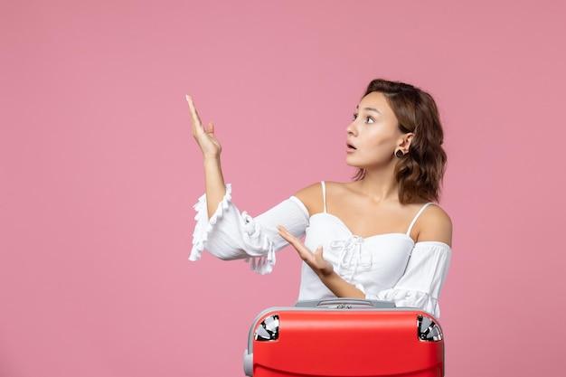 Vista frontale della giovane donna che posa con la borsa rossa delle vacanze sulla parete rosa