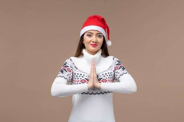 Giovane donna di vista frontale che prega e che sorride sul natale marrone di emozione del nuovo anno del fondo