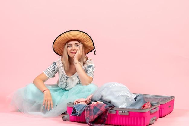 旅行の準備とピンクの背景色の旅行航海休暇休憩服で彼女の服を分解する正面図の若い女性