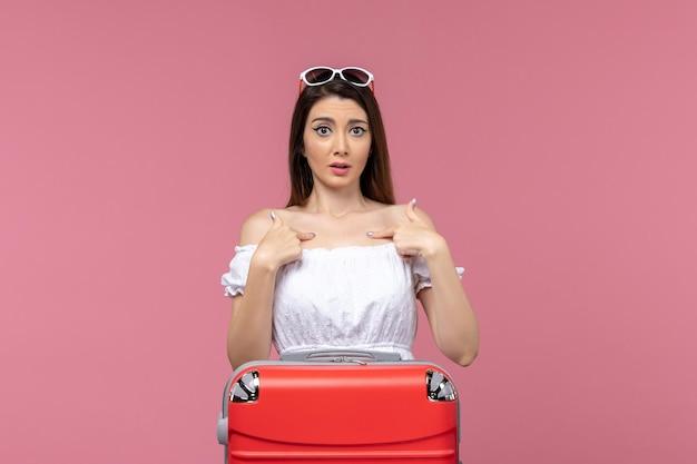 ピンクの背景の旅行旅行女性の航海海で彼女のバッグと一緒に休暇の準備をしている正面図