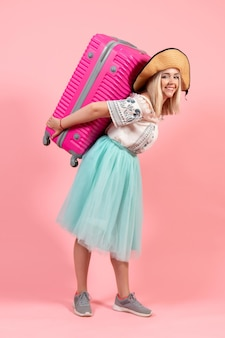 Vista frontale giovane donna che si prepara per le vacanze estive che trasportano borsa rosa su uno sfondo rosa viaggio viaggio vacanza mare aereo resto colore